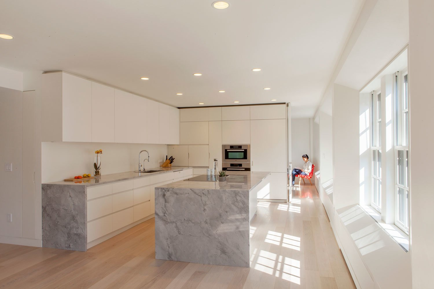 A series of bedrooms was replaced by an open-plan living arrangement. The kitchens are White Fantasy quartzite paired with white lacquered millwork.  Architecture Firm You Should Know: Höweler + Yoon by Allie Weiss
