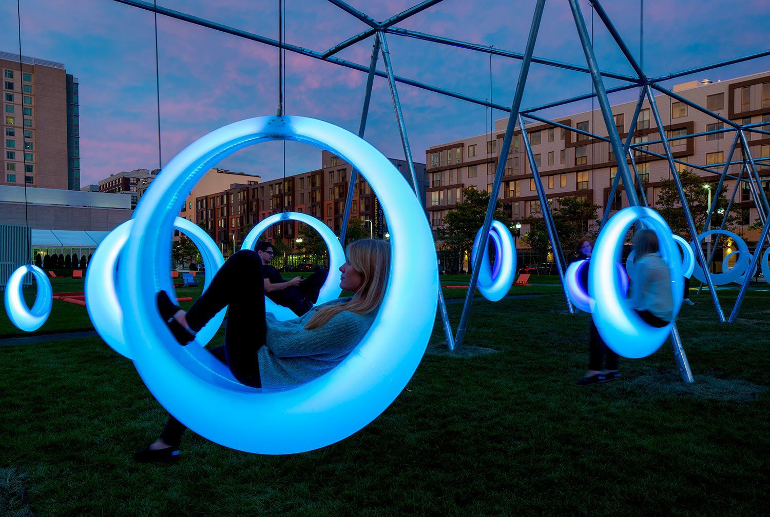 An installation brought 20 circular, glowing swings to a grassy area near the Boston Convention Center. LED lights embedded in the polypropylene swings change color depending on its motion.  Architecture Firm You Should Know: Höweler + Yoon by Allie Weiss