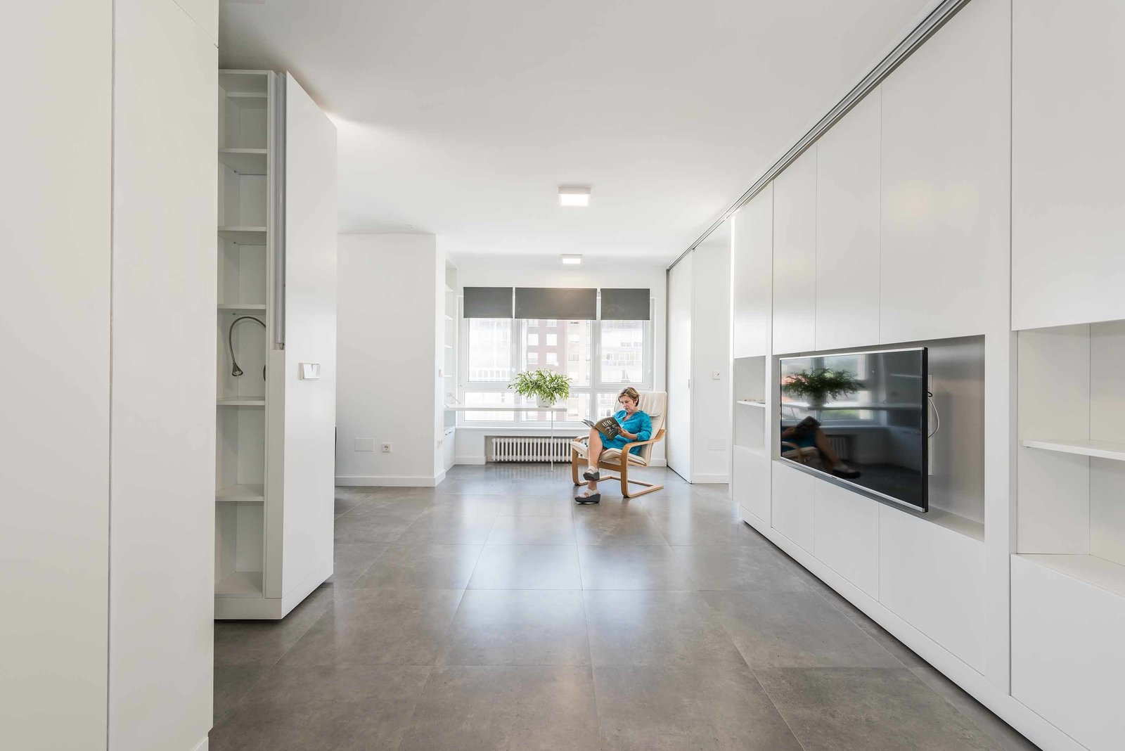 """Living Room, Ceramic Tile Floor, Ceiling Lighting, Storage, and Chair Viewed from the entryway, the living room is the main gathering space of the home. Dated parquet floors were replaced with modern ceramic tile. All walls and ceilings were re-plastered, and old windows were upgraded with energy-efficient double-glazed glass.  Search """"entryway"""" from Movable Walls Instantly Transform a Small Vacation Home from a Two-Bedroom to a Studio"""