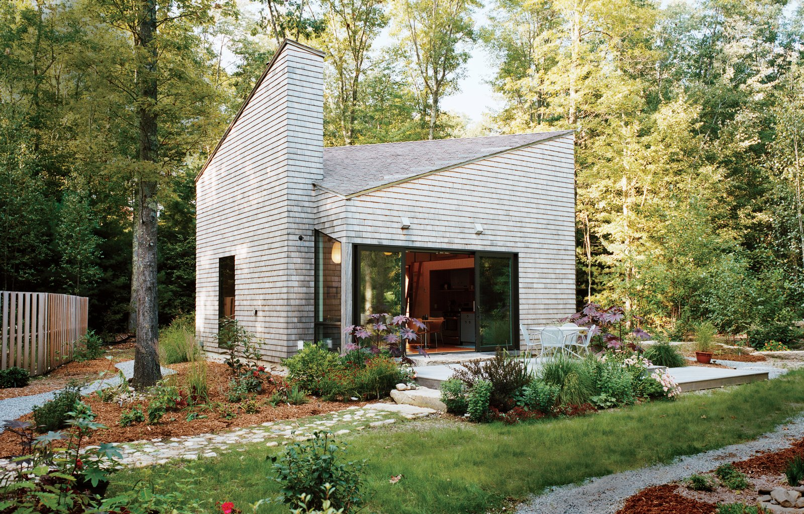 Exterior, Tiny Home Building Type, Wood Siding Material, and Shingles Roof Material An artist by trade, and gardener by passion, Allison Paschke commissioned Providence-based architecture firm 3SIXØ to build a modest cottage that would allow her to reconnect with nature. She landscaped the home's lush gardens herself.  Best Photos from This Tiny New England Cottage Is a No-Frills Weekend Hideaway