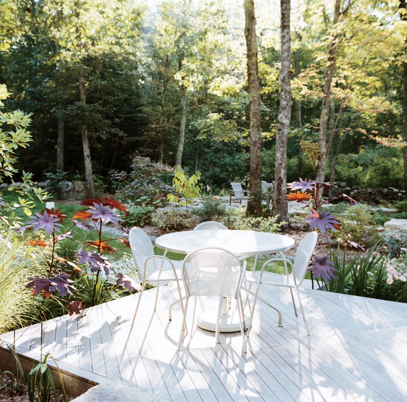 Outdoor, Wood Patio, Porch, Deck, and Small Patio, Porch, Deck The deck is furnished with pieces from Design Within Reach.  Photo 2 of 12 in This Tiny New England Cottage Is a No-Frills Weekend Hideaway