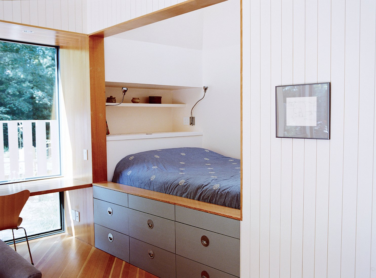 Bedroom, Shelves, Medium Hardwood Floor, and Bed Key to the space-efficient floor plan is a strategically placed set of recessed areas, includingthe sleeping nook and writing desk.  Photo 4 of 12 in This Tiny New England Cottage Is a No-Frills Weekend Hideaway