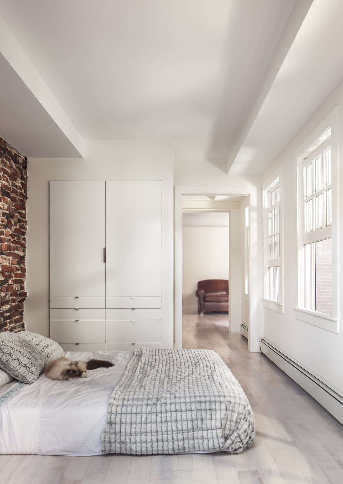 Bedroom, Bed, and Light Hardwood Floor The renovation revealed a 30-foot-deep well beneath the bedroom, which the team half-jokingly considered turning into a fish tank. Instead, they opted for a simple bedroom with plenty of built-in storage.  Bedrooms by Dwell from Beacon Hill