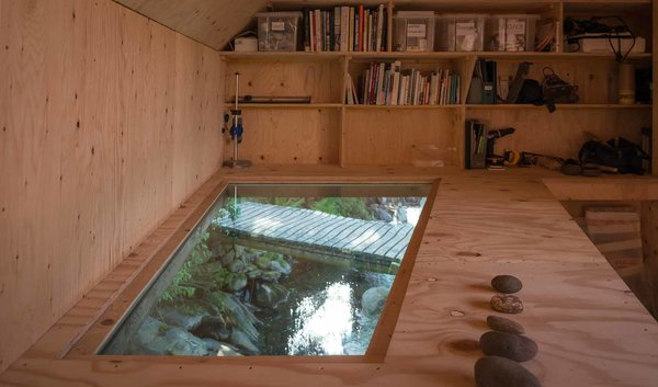 """A 'light soffit' offers a dynamic view of the stream below, providing both visual and audio stimulation. Throughout the year, the studio is filled with the sound of water, from the ocean waves to the rain and drizzle, to the flowing stream below. The artist, who has a longstanding connection to the site, focuses on """"art which leaves marks at once permanent and delicate,"""" much like the structure itself."""
