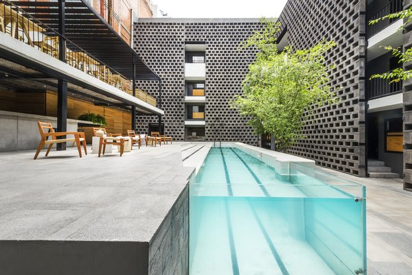 Outdoor Originally dating to the 1970s, Hotel Carlota was revamped by JSa Arquitectura and completed in 2015. As part of the renovation, a pool became the focal point of the courtyard, and its modernized, streamlined design makes a dramatic statement.  Photo 8 of 11 in 5 Striking Designs That Use Perforated Cement Breeze-Blocks in Interesting Ways