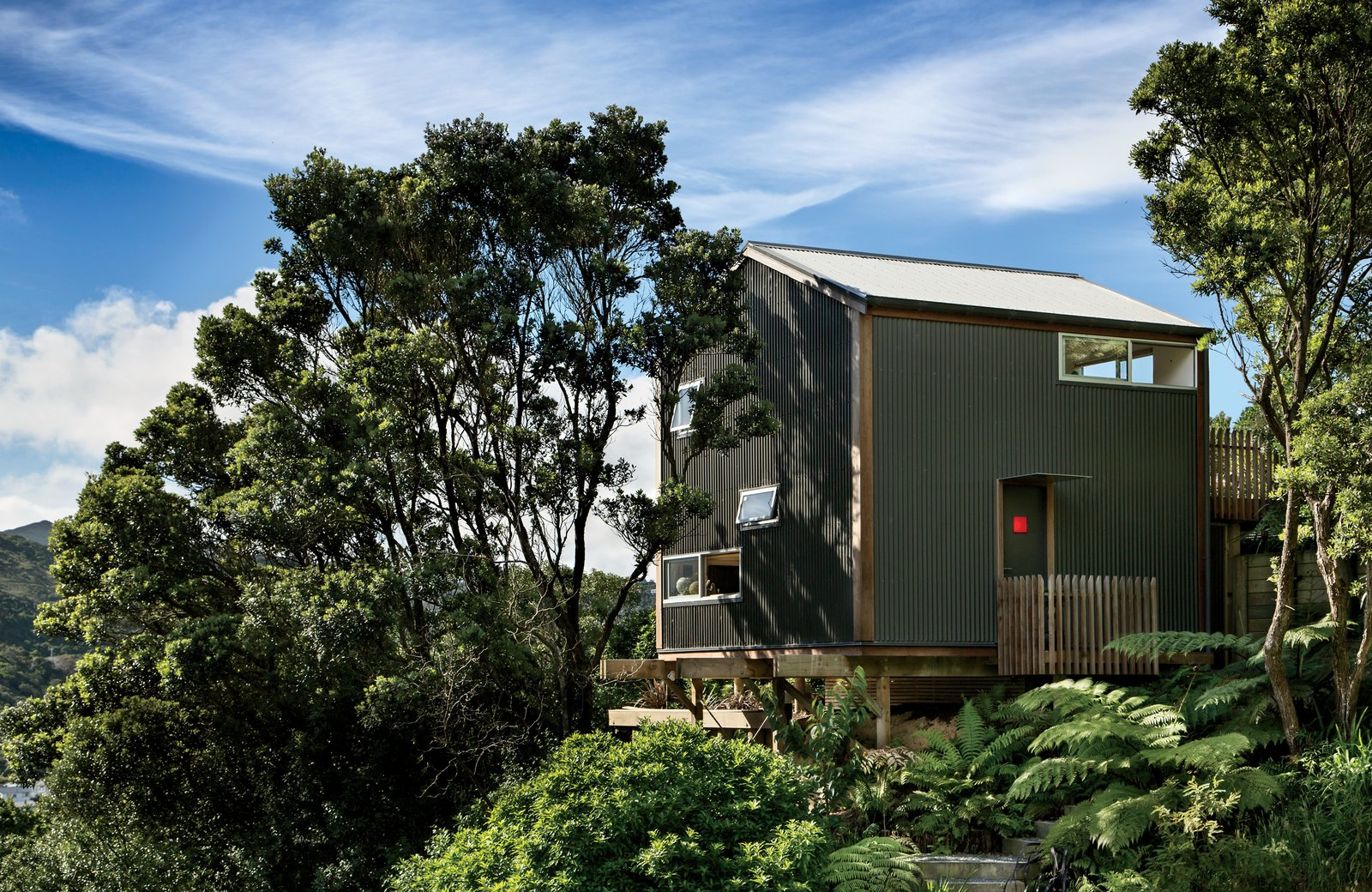 Exterior, House Building Type, Metal Siding Material, Gable RoofLine, and Metal Roof Material Inspired by the small scale of Japanese residences—in particular, Makoto Masuzawa's 1952 Minimum House—architect Andrew Simpson designed his own economical 538-square-foot home, set into a wooded site in Island Bay, a coastal suburb outside Wellington, New Zealand.  Small Spaces from A Home's High Ceilings Are Responsible for Some Impressive Views