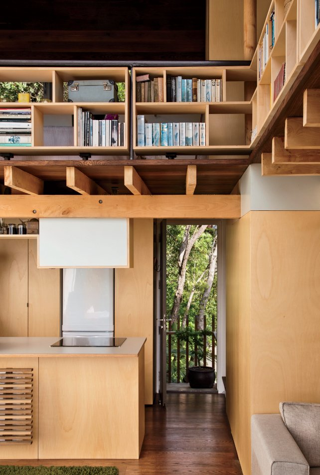 Storage Room and Shelves Storage Type Architect and resident Andrew Simpson maximized the diminutive home with double-height ceilings, elevated compact shelving, and lofted sleeping quarters.  Photo 2 of 10 in A Home's High Ceilings Are Responsible for Some Impressive Views