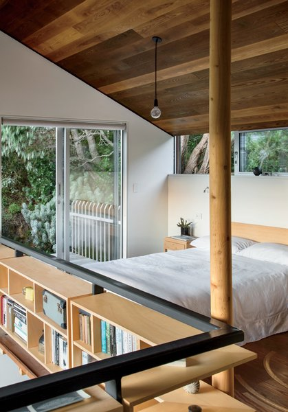"Bedroom, Bed, Storage, Bookcase, Pendant Lighting, Night Stands, and Medium Hardwood Floor ""Being your own client is very difficult, and different from the standard process—you get to be more experimental.""—Andrew Simpson, architect and resident  Bedrooms by Dwell from A Home's High Ceilings Are Responsible for Some Impressive Views"