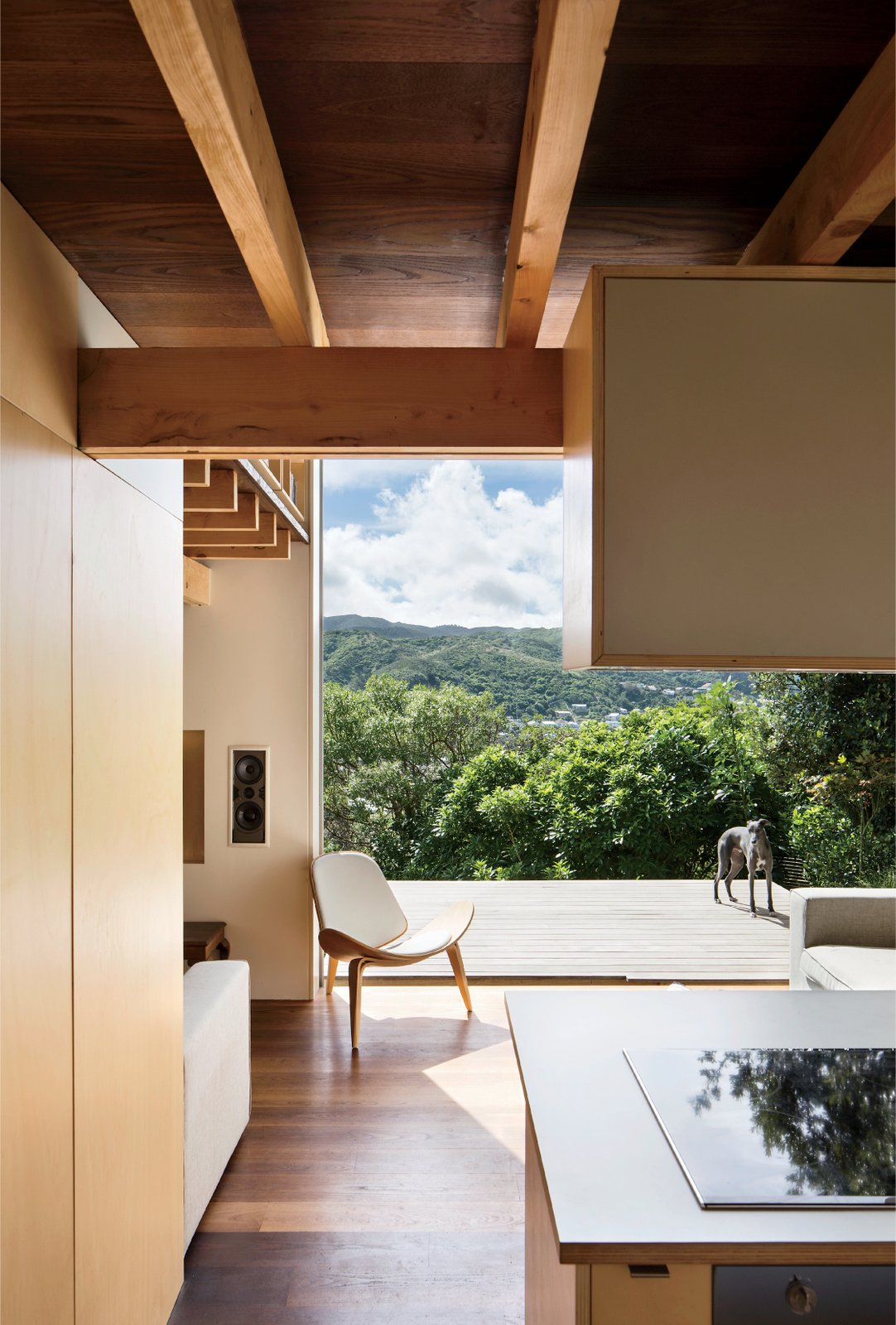 Living Room, Chair, Sofa, and Medium Hardwood Floor The home also extends into outdoor panoramas, even—and especially—from the ground floor, where a westward-facing deck cantilevers out into the lush landscape.  Small Spaces from A Home's High Ceilings Are Responsible for Some Impressive Views