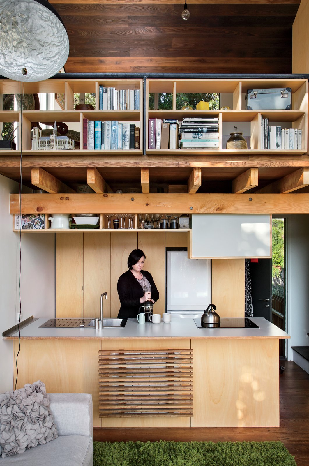 Kitchen, Wood Cabinet, Drop In Sink, Cooktops, Pendant Lighting, Refrigerator, and Medium Hardwood Floor On the ground floor, Simpson's fiancée, Krysty Peebles, makes coffee in a compact kitchen outfitted with a Foraze Panni sink, Bosch induction cooktop, and Mitsubishi refrigerator.  Solutions For Tiny Kitchens by Aileen Kwun from A Home's High Ceilings Are Responsible for Some Impressive Views