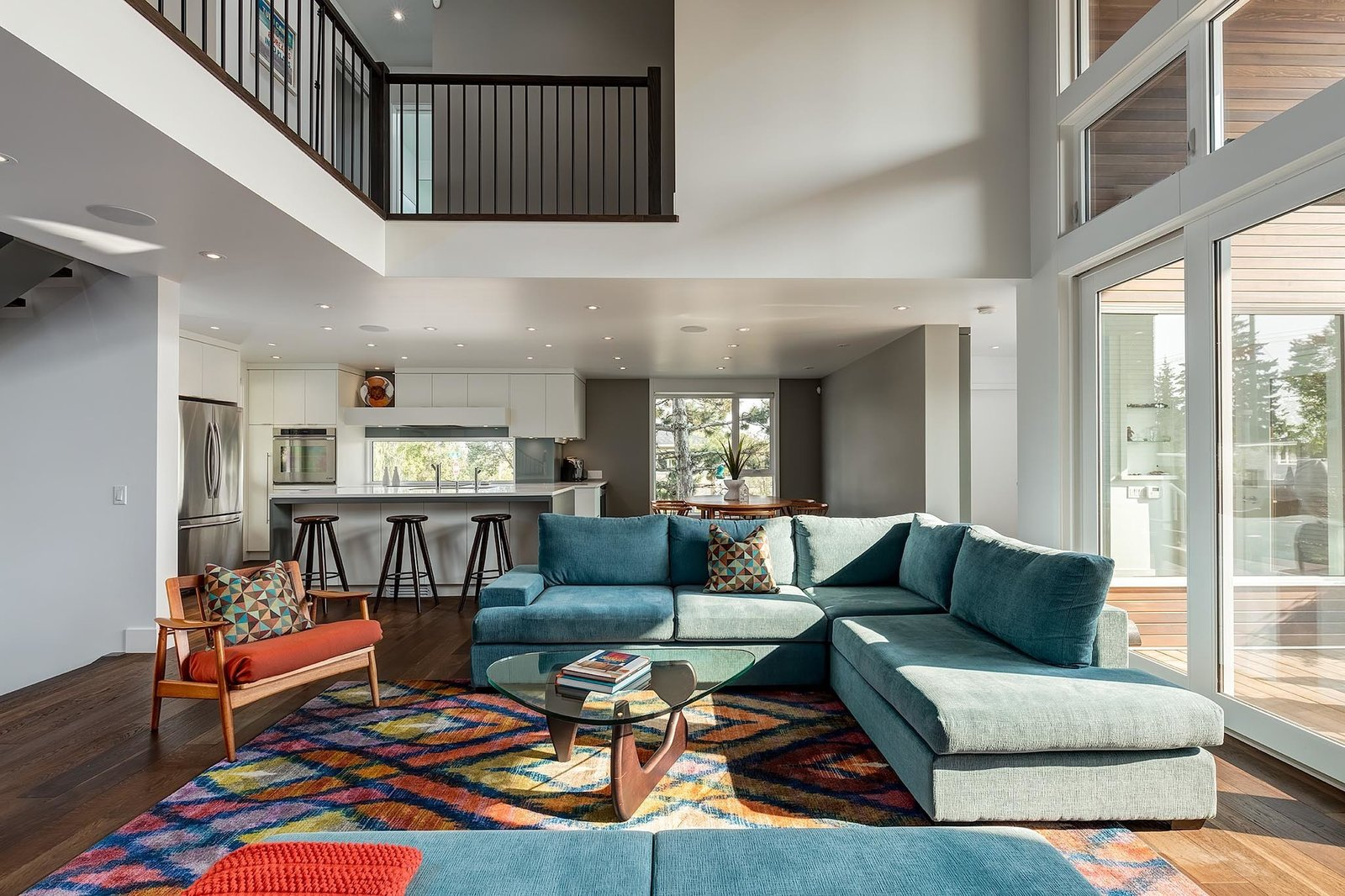 """""""The home's color pallet in terms of walls, floors and cabinetry is very neutral and minimal, which allows for splashes of color to be added tastefully with furniture and art pieces,"""" Lewis said. C2 Paint's """"Architectural White"""" and American oak flooring act as a backdrop.  A Calgary Home Makes Space for Three Generations by Kelly Dawson"""