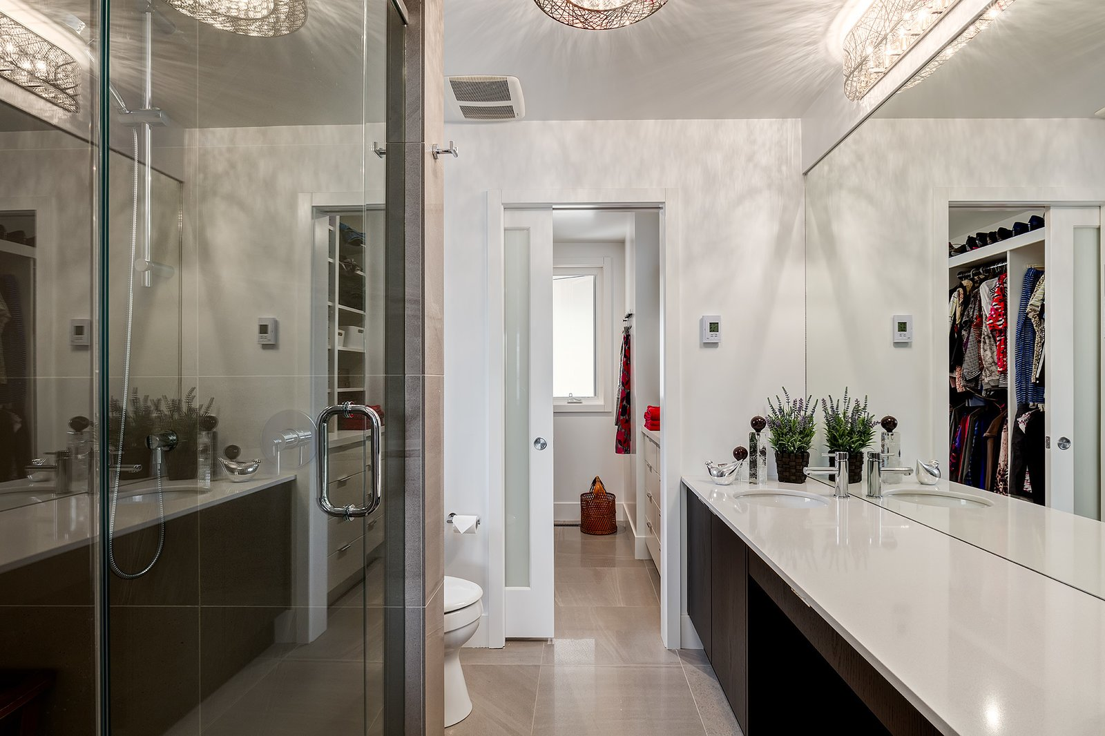"""The mother's en-suite bathroom, like all bathrooms in the house, has the same Caesarstone """"eggshell"""" countertops as the kitchen. Kartners """"Oslo"""" collection makes up all of the bathroom's hardware.  A Calgary Home Makes Space for Three Generations by Kelly Dawson"""