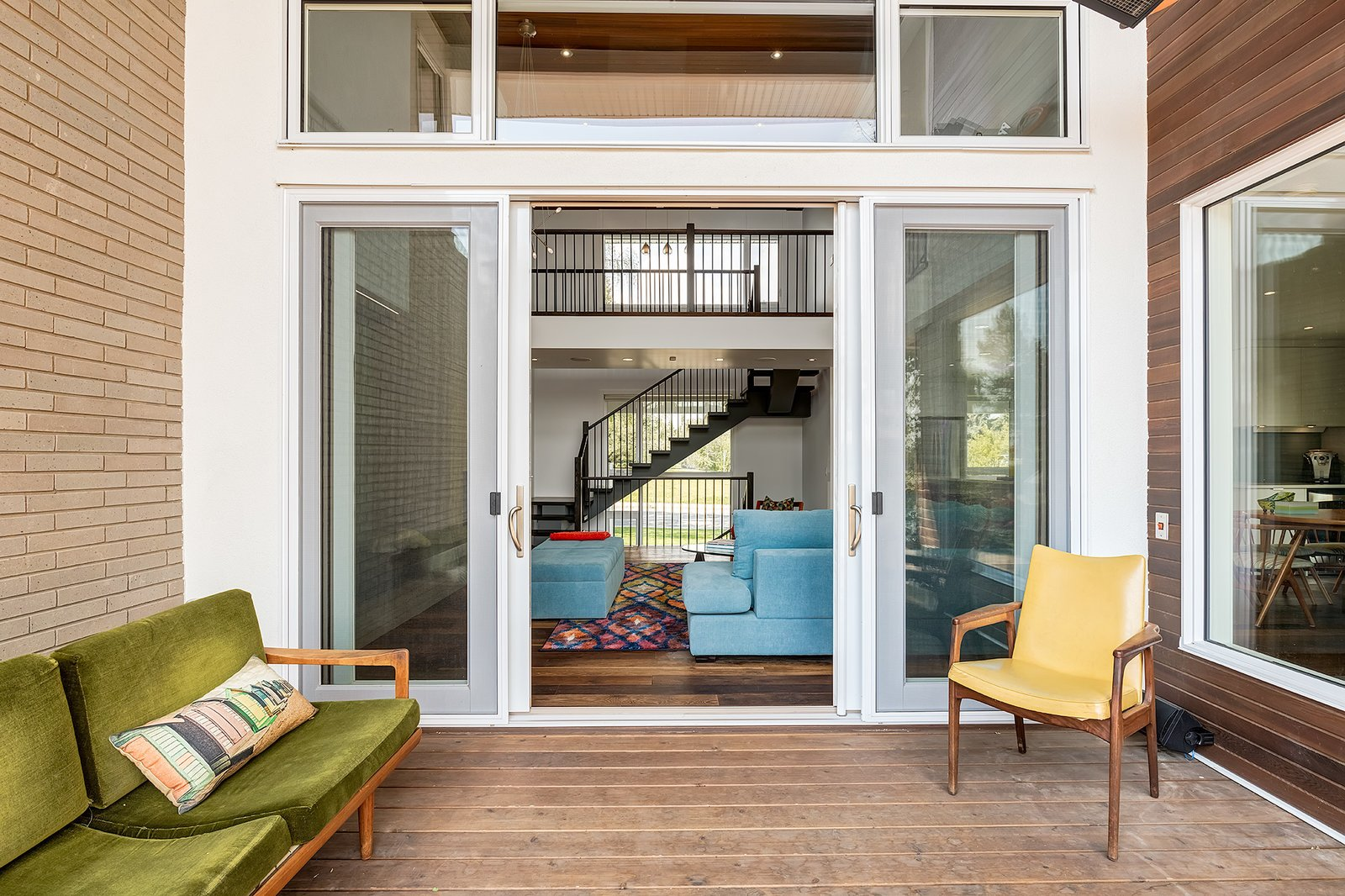 """The homeowners love to watch golf, and so the outdoor space was designed so that the T.V. can be easily viewed for comfortable, outdoor summertime golf watching,"" Lewis said. Vintage pieces furnish an outdoor deck of stained cedar.  A Calgary Home Makes Space for Three Generations by Kelly Dawson"