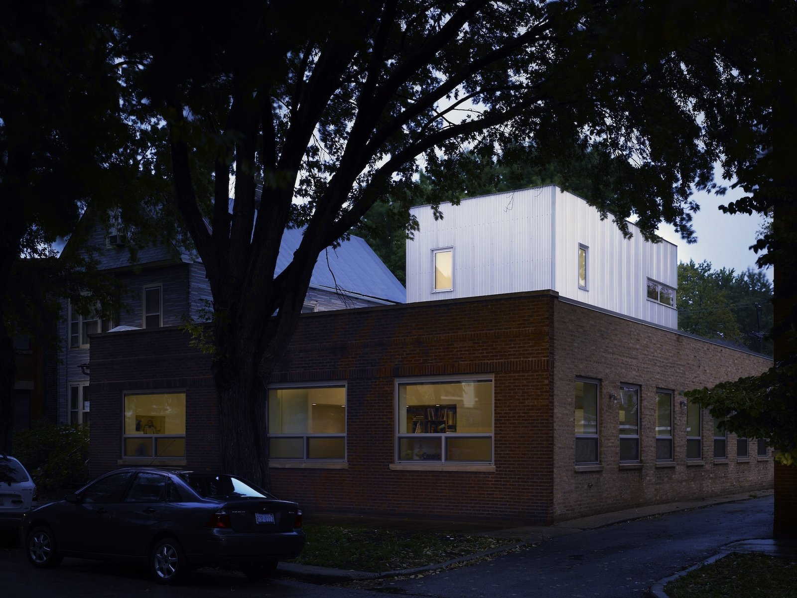 Appearing almost as a glowing container stack, the corrugated aluminum addition relates to the low-lying structure's commercial past. Not that owners Dave and Jeannette Jordano were saddled with rehab and remediation. The previous occupant, architecture firm Morgante Wilson, outgrew the 50-foot-by-50-foot footprint but left the space in fine condition.  Ravenswood Residence by Ian Spula