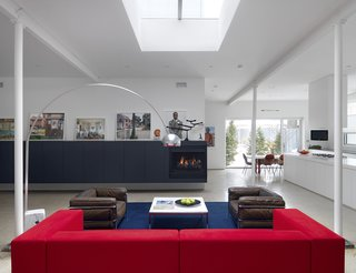 A new skylight regulates the living room's natural light. Ronan set up great contrasts in the space with the bone white walls and ceiling, black wall unit with built-in fireplace, and the crisply framed courtyard. The owners enhanced the space further with vibrant photography and furnishings.