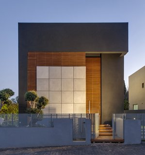 The home's facade is private and mysterious, without discernable windows or openings. The exterior is made of concrete tiles, black plaster, and wooden trellises. The trellises act as a light screen, allowing only cracks of light to penetrate the exterior. The entry is camouflaged in the plane of the trellises, which adds to the opaque and impenetrable aesthetic at the front facade.