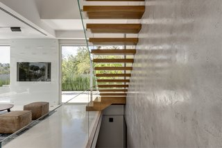 Inside, the home immediately opens up with light and natural views. The cantilevered stairs leading to the first floor offer a dramatic focal point. The stairs, wrapped in natural oak, are anchored to the exposed concrete walls on one side, and bordered by a clear glass railing on the opposite side.