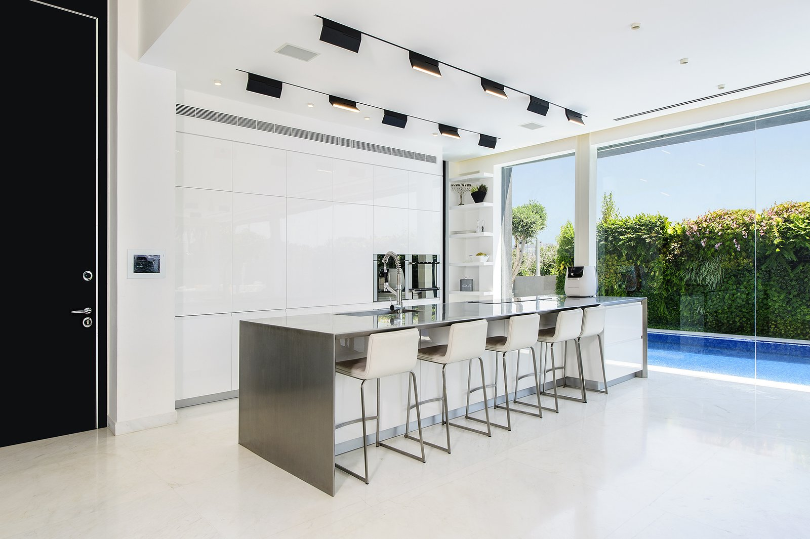 A well-lit and open ground floor with a strong interior-exterior connection was at the top of the family's wish list. The kitchen makes the most of a compact space through its intimate relationship with the adjacent pool and public outdoor space. The spaces features hardware-free white cabinets and a stainless steel center island. The white kitchen floors provide visual continuity with the white pavement directly outside.  Rishon Le Zion 3 by Sarah Akkoush