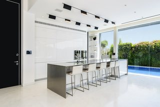 A well-lit and open ground floor with a strong interior-exterior connection was at the top of the family's wish list. The kitchen makes the most of a compact space through its intimate relationship with the adjacent pool and public outdoor space. The spaces features hardware-free white cabinets and a stainless steel center island. The white kitchen floors provide visual continuity with the white pavement directly outside.