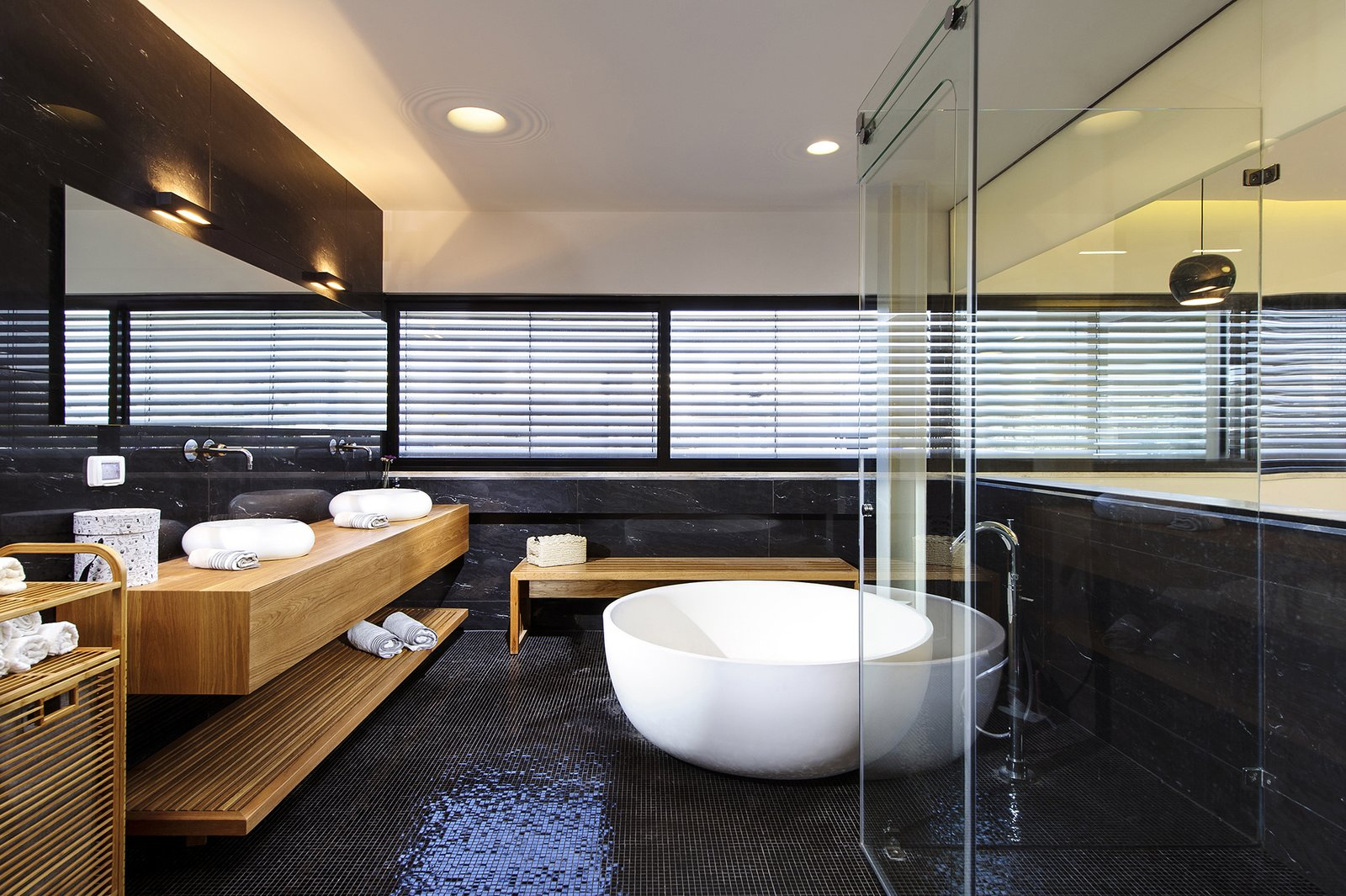 The sleek master bathroom features a freestanding tub, black mosaic tiles on the floor, and black natural stone on the walls. A natural oak vanity and oak accents add warmth to the otherwise cool and contemporary space, and a glass wall on the opposite side creates a sense of connection with the master bedroom.  Bathroom from Rishon Le Zion 3