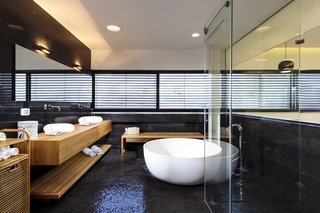 The sleek master bathroom features a freestanding tub, black mosaic tiles on the floor, and black natural stone on the walls. A natural oak vanity and oak accents add warmth to the otherwise cool and contemporary space, and a glass wall on the opposite side creates a sense of connection with the master bedroom.