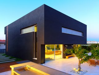 The voluminous black plaster cube appears to float over the open first-floor at the rear elevation. On the roof, solar panels generate about 80 percent of the home's electrical and heating needs. The landscaped backyard was designed to resemble an orchard, and includes several defined areas for socializing and entertaining.