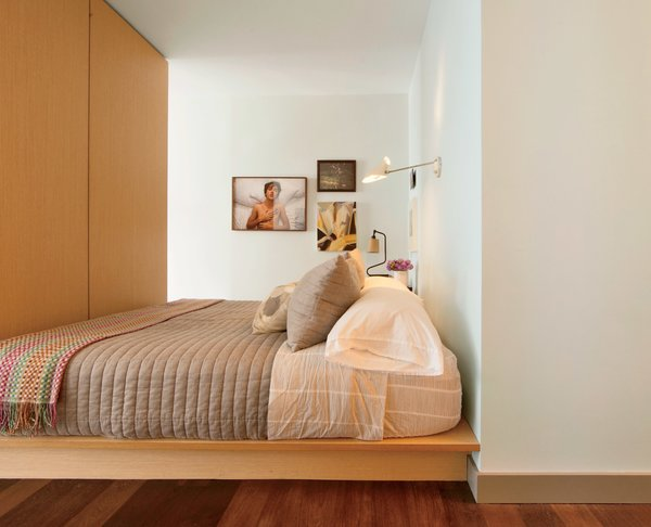 If sleek storage is what you're looking for, consider a long and low platform bed. At a New York apartment that's just over 500 square feet, the wood platform bed features storage panels under the mattress.
