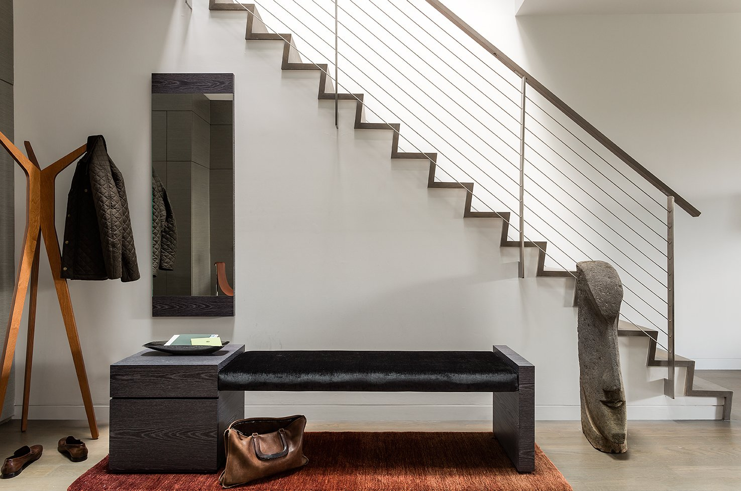 """""""The entire house is unified with oak flooring with a custom warm gray stain. This material is repeated on the stair and atrium handrails,"""" Walker said. The entryway's bench has a custom Tabu Caleidolegno veneered wood base. The upholstered bench seat, which uses black Kravet fabric, was designed by Ruhl Walker Architects and made by Herrick & White.  Back Bay by Kelly Dawson"""
