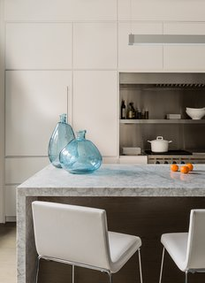 Lineal Comfort stools upholstered in white leather by Andreu World sit across from turquoise glass vases from Neiman Marcus. Cumar supplied the white carrara marble for the island.