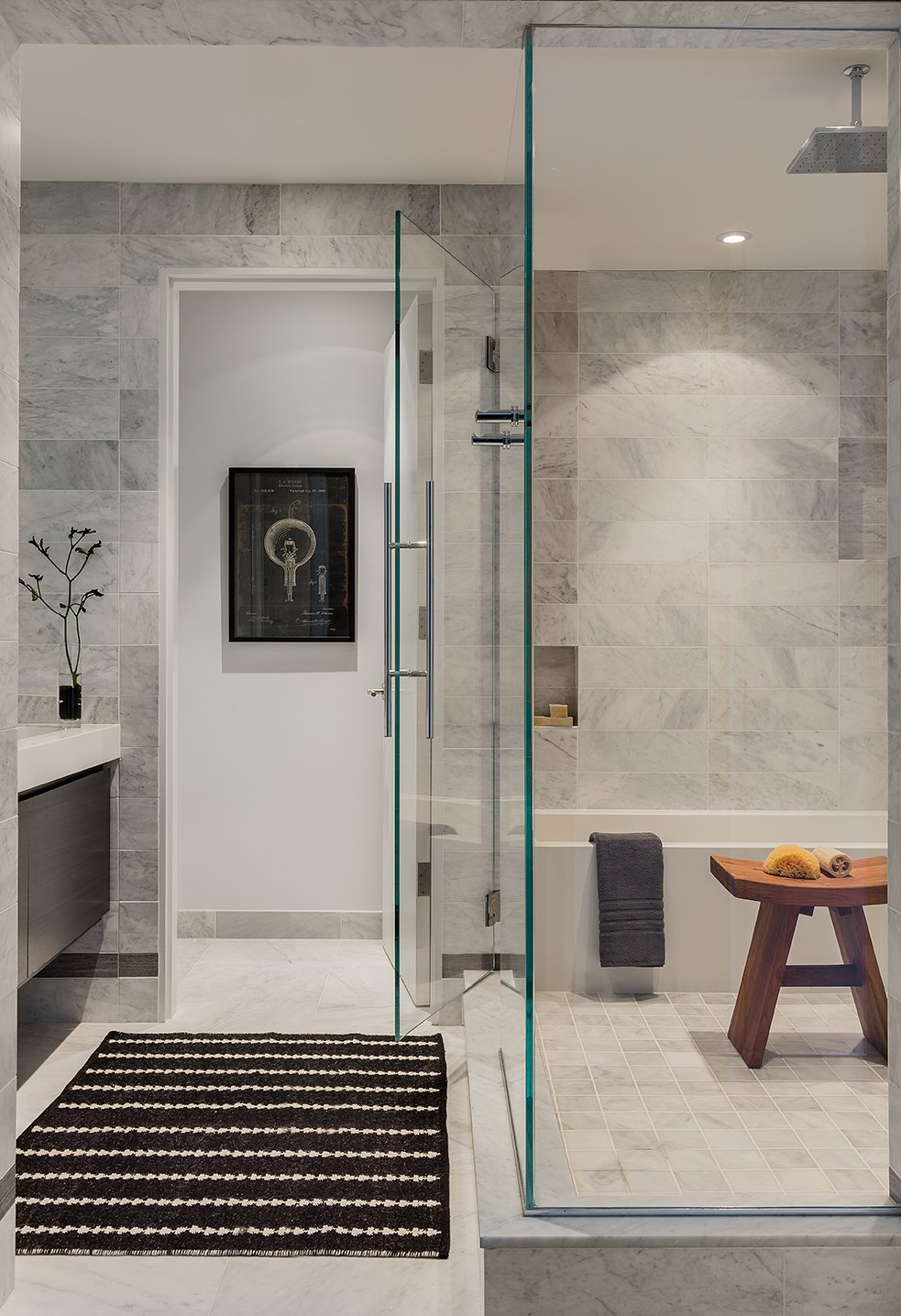The master bathroom's marble tile wall is by White Venatino marble, with gray accent tile from Florim USA. A Wetstyle bathtub stands in the corner.  Back Bay by Kelly Dawson