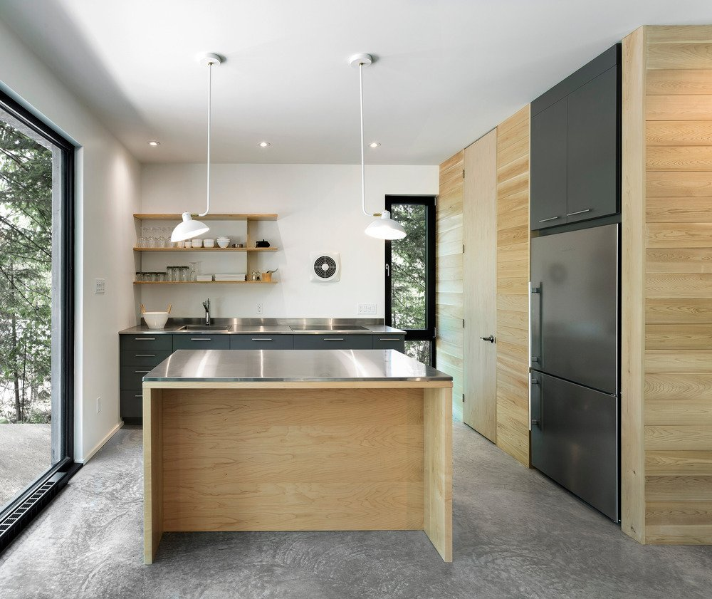 The Spahaus model is modular and available in five configurations. They vary in size from 1070 square feet to 1420 square feet. In the kitchen, gray laminate cabinets are topped with stainless steel countertops.  Spahaus by Allie Weiss
