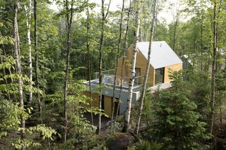 The facade consists of exposed concrete, Galvalume roofing, and cedar or torrefied wood coating. The homes are carefully positioned to keep other structures out of sight.