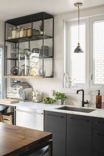 In a centuries-old building in Montreal, Belgian architect and designer Gaeten Havart undertook a DIY kitchen renovation that makes the most of inexpensive materials. These simple cabinets and modern cabinet pulls are from Ikea and painted with a matte black finish.