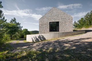 Resembling its neighbors, the pitched form of the Compact Karst House is made of a mixture of local limestone and concrete, cast on site. A small perimeter wall in reinforced concrete surrounds the structure.