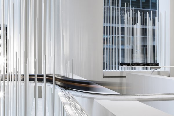 The display features hundreds of freestanding white rods that create a hyper-minimal snowscape.