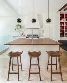 In the mostly-white kitchen, black Topan pendants by Verner Panton pop. The butcher block counters are an unusual height, so Lee designed custom-made stools to fit.
