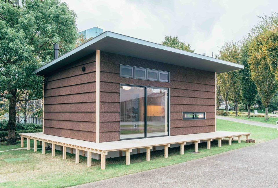 The second Muji Hut, by British designer Jasper Morrison, who splits his time between his studios in Paris and Tokyo, features dark brown cork cladding, a timber porch, and gently sloped roof.  Muji Hut Launches With 3 New Tiny Prefab Homes by Aileen Kwun