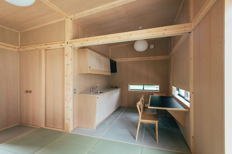 It also includes a small kitchenette equipped with a sink, wooden countertop, and a dining area/nook. The door to the left leads to a bathroom.  Muji Hut Launches With 3 New Tiny Prefab Homes by Aileen Kwun