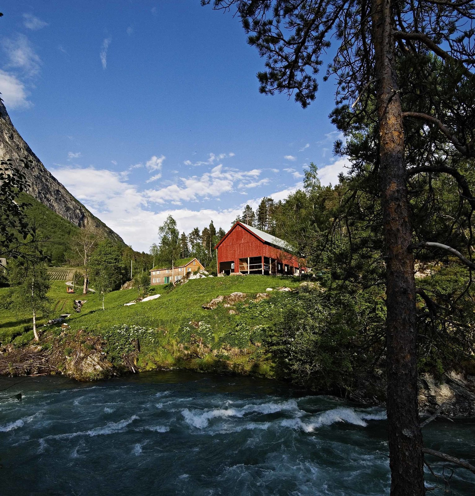 Outdoor, Slope, Trees, and Grass The Juvet is tucked into the woodsy corner of a classic Norwegian farm on the banks of the rushing Valldola River. The farm has existed here since at least the 1500s.  Photo 3 of 8 in Rustic Cabins Comprise This Impossibly Idyllic Hotel in Norway