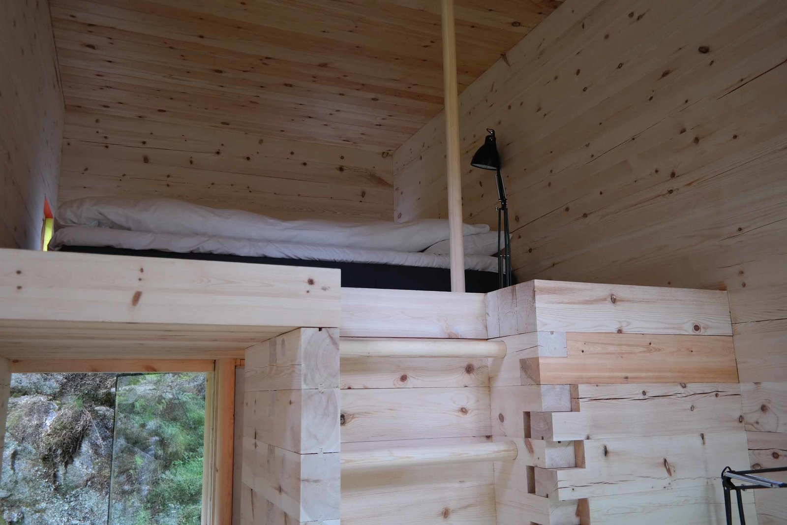 Bedroom, Bunks, Bed, Lamps, and Floor Lighting The new cabins' pine interiors have been left their natural shade. Furnishings are kept to the absolute minimum to keep guests' focus on what lies outside.  Photo 6 of 8 in Rustic Cabins Comprise This Impossibly Idyllic Hotel in Norway