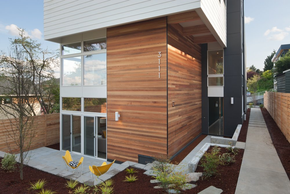 """""""The local cedar and Douglas fir used inside and outside creates a simple, elegant, and timeless feeling for the home,"""" said Weber. The wood exterior was installed below exterior lap siding painted Benjamin Moore's """"Glacier White.""""  Cedar Douglas Residence by Kelly Dawson"""