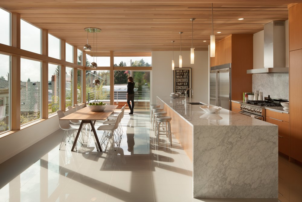 The ceiling on the main level of the home was built to reflect the same clear-stained cedar on the exterior. The mini pendants above the kitchen's waterfall island—which is made of Carrara marble—are by Minka Lavery.  Cedar Douglas Residence by Kelly Dawson