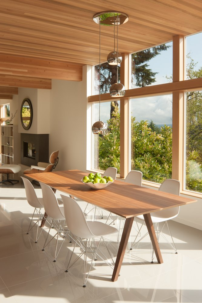 """""""We used extensive glazing in the kitchen, dining, and bedroom areas to capture views of Lake Washington and downtown Bellevue across the water,"""" Weber said. The chrome chandelier above the dining table is by Artcraft Lighting.  Cedar Douglas Residence by Kelly Dawson"""