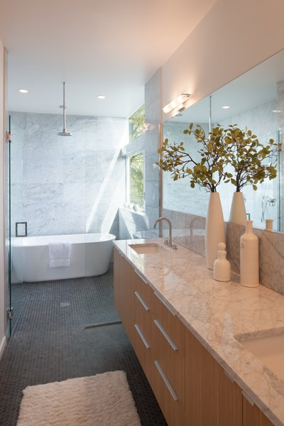 Edgewood cabinets adjoin countertops made from Carrara marble in the master bathroom. A Wyndham Collection bathtub sits under a chrome showerhead by Moen.