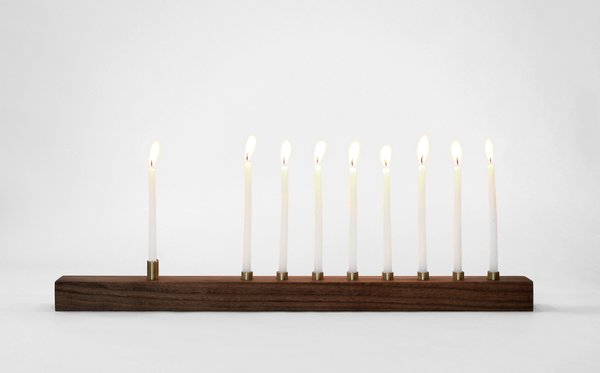 Celebrate Hanukkah this year with the elegant walnut menorah from Marmol Radziner. The menorah is handcrafted from solid walnut wood and bronze, giving it a one-of-a-kind quality that is met with a rich, warm look. With illuminated candles, the wood and bronze gives off a soft reflective glow, which is aided by the mineral oil finish to the walnut wood.