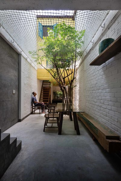 By merging typical Saigon architectural and stylistic details, architect Toan Nghiem of a21 Studio created a space that brings family together. Stacking roof layers, open flowering balconies, and an alleyway that serves as a living room, dining room, and outdoor playground are all filled with colorful, rich materials. Inside Saigon House, reclaimed and second-hand furniture lend history and spirit to the home. With so many small interior rooms and divisions between spaces, the addition of a net ceiling brings openness to the back alleyway, where the family often gathers to eat dinner. Not only does the net allow for ventilation and light, but it offers a place to play for the children, who love to climb and lounge above their parents.