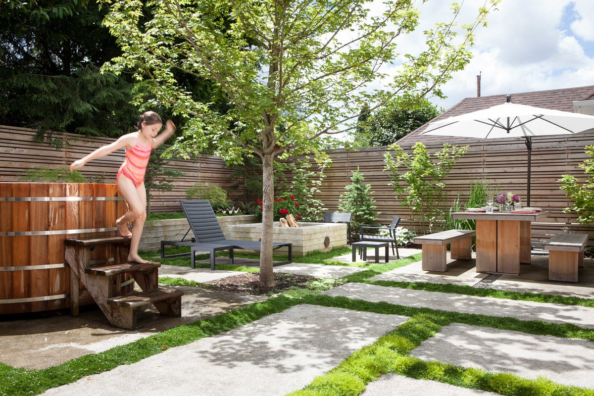 Outdoor, Pavers Patio, Porch, Deck, and Back Yard A 2,500-square-foot backyard off a Portland home was completely overhauled by architect Michael Howells. Its new design uses pavers to divide the yard into sections that include planters, a cedar soaking tub, and a fire pit.  Photo 8 of 11 in 10 Modern Hot Tubs from Japanese-Inspired Backyard with a Tiny Studio in Portland