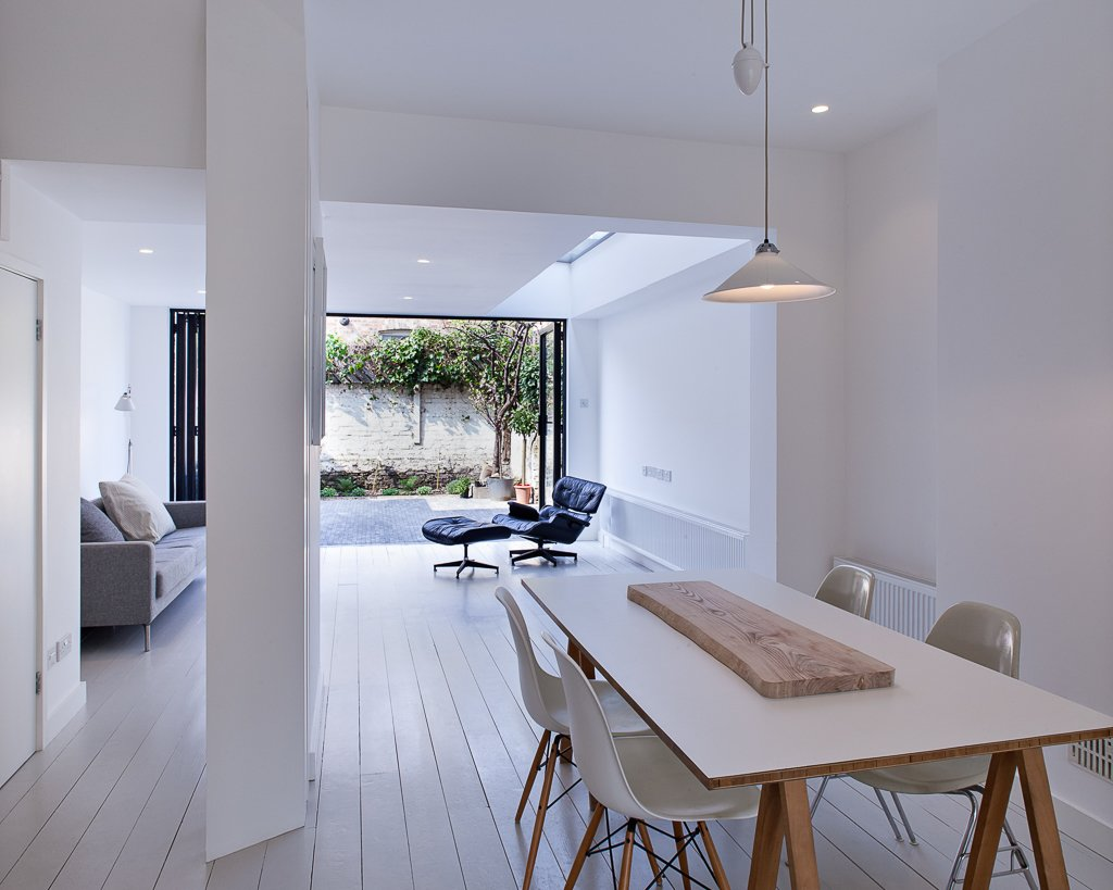 The ground floor of the home is both the clients' and architects' favorite part of the home. The opened living room fulfills the owners' wish for a private and quiet sanctuary connected to the rear garden yet removed from the noise of the front street. A key design feature was the widened rear opening, with floor to ceiling aluminum-framed Comar glass doors.  Brilliant Examples of Indoor-Outdoor Homes by Zachary Edelson from A Compact, Light-Filled Victorian Renovation in England