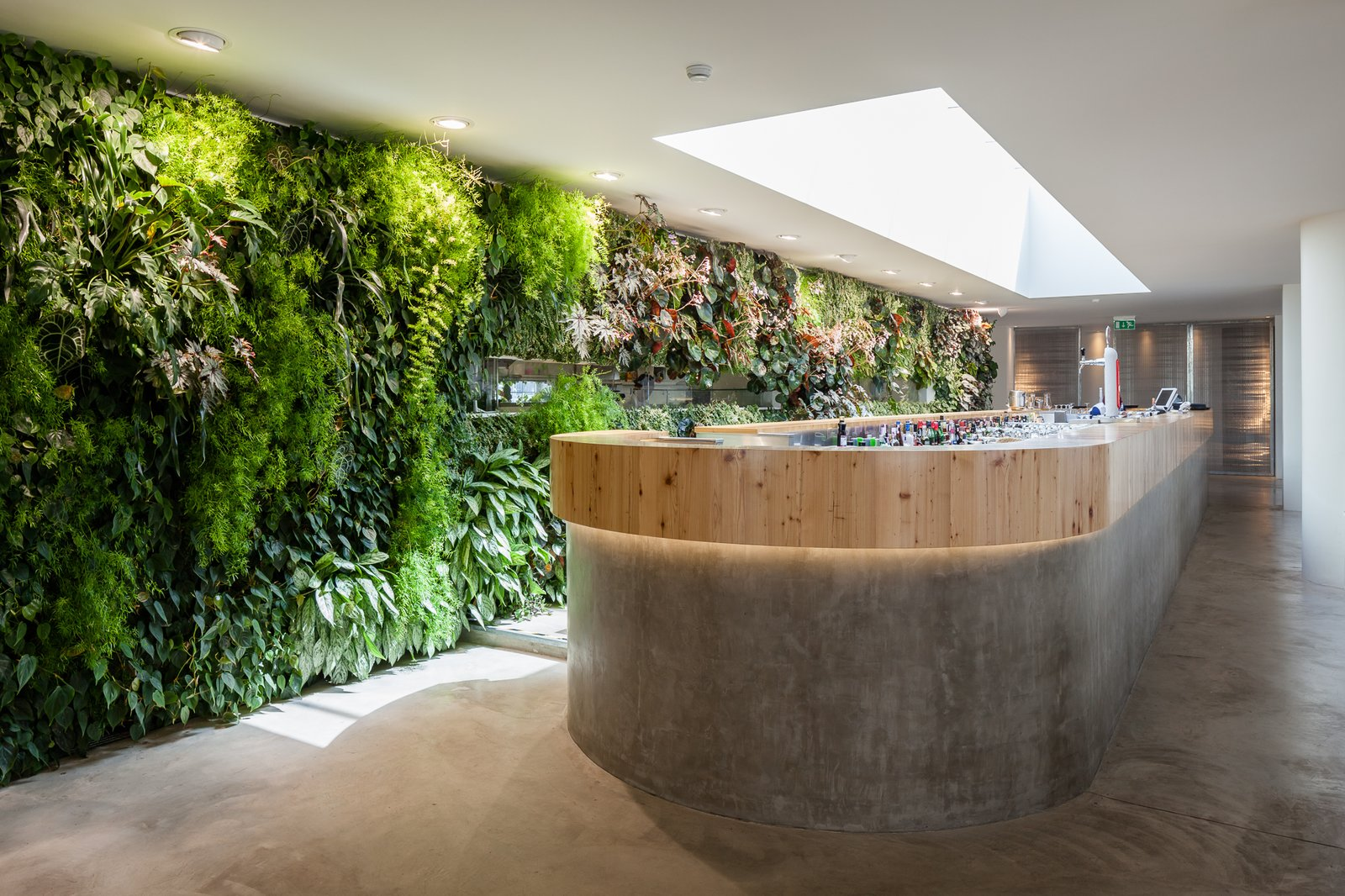 A custom bar sits underneath a retractable skylight. The material palette of the interior is simple, with white walls and concrete flooring.  Vertical Gardens Spruce Up a Dusty Monument by Allie Weiss