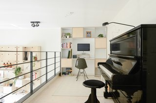 The loft addition afforded space for a home office and music area. The family chose to forego a dedicated office upstairs, instead prioritizing private bedrooms for each of the children. Shelving and a built-in desk anchor the loft's far wall.